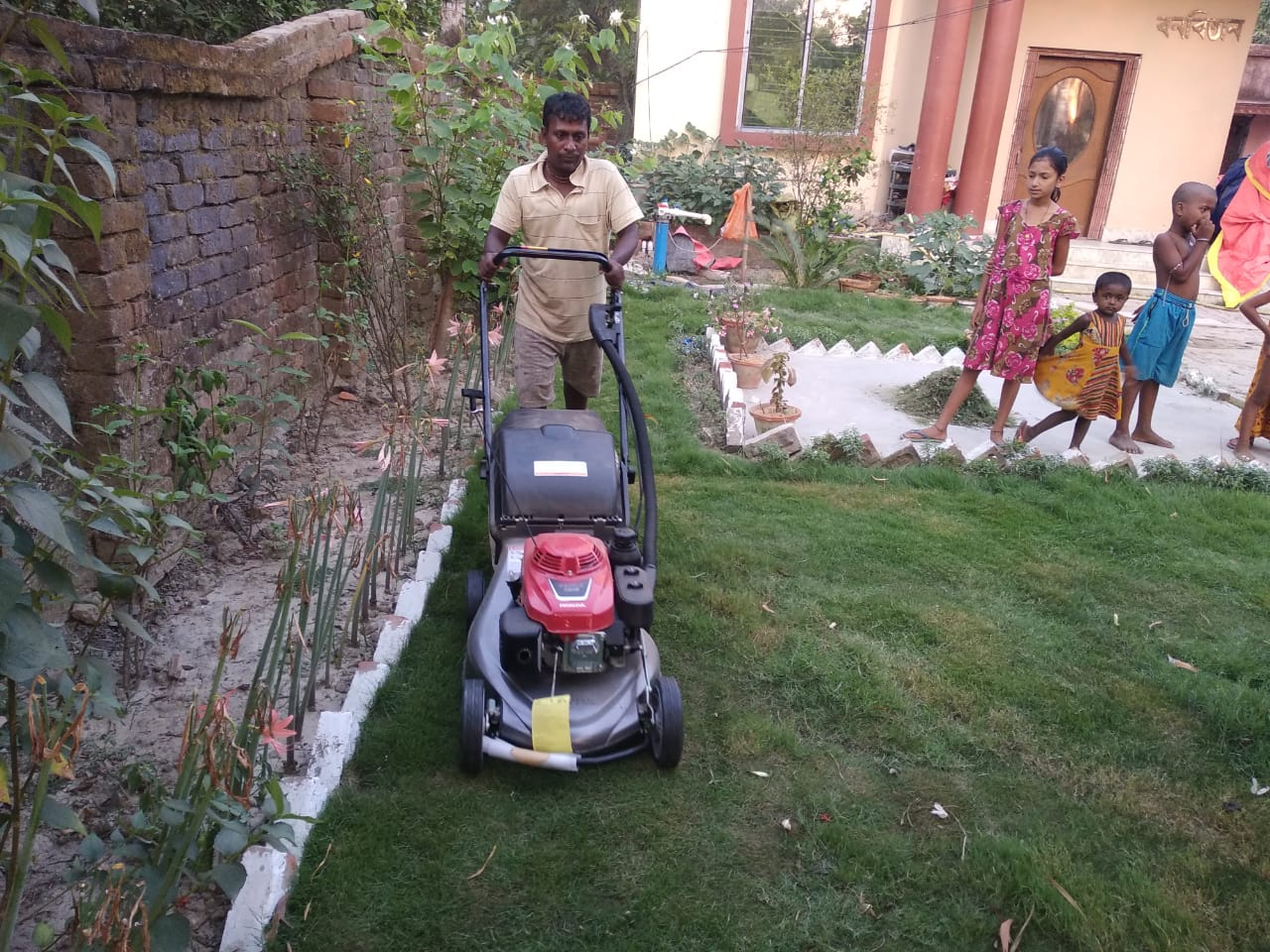 Grass Cutting Work Beside The Roadside Lawn Is Going At Mukti Gram